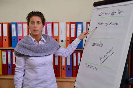 Seminar leader explains course contents on flipchart Stock Photo