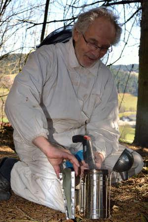 apiarist: Beekeepers preparing Smoker ago for his work