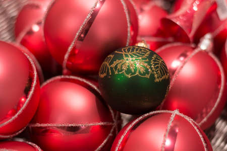 misfit: Close-up abundance of red Christmas baubles with a green Stock Photo