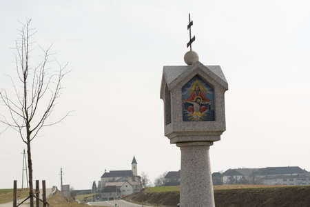 a rural community: roadside shrine from granite in front of a rural community - - Austria Stock Photo