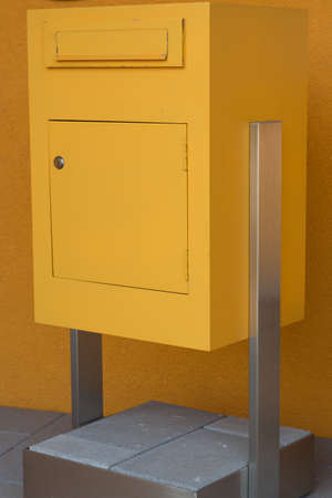 reachability: big yellow mailbox on concrete base before yellow house