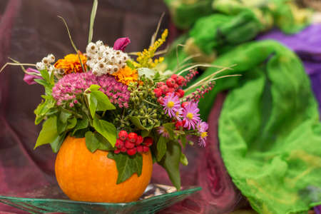 colorful autumn decoration with pumpkin and bright colorful flowers