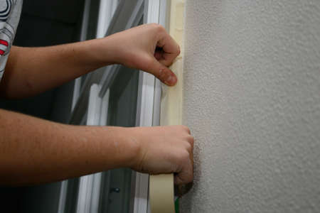 masking: Masking tape to window frames - Person at preparatory work prior to repainting