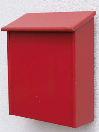 reachability: bright red post box made of wood Stock Photo