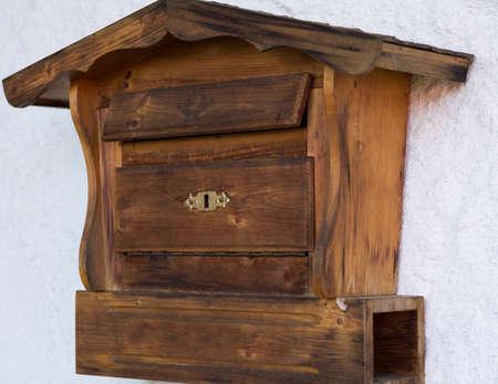 lockbox: Wooden mailbox with newspaper roll Stock Photo