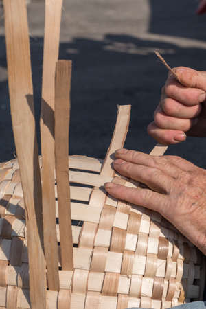 contributed: Person weaves a rocker - Couffins Stock Photo
