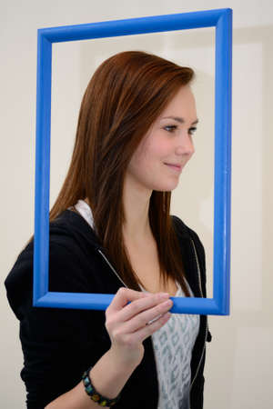 look pleased: side profile of a teenage girl behind a picture frame