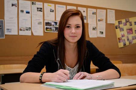 schoolroom: Teenager writes in the classroom