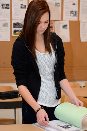 sorts: Teenager arranges and sorts documents in a folder