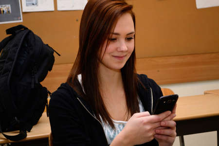 net surfing: Teenager sitting in class and write sms in the break Stock Photo