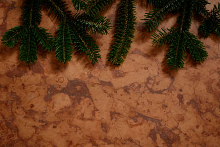 patterning: red marble with hanging out from the top of fir branches - Background and Copy Space Stock Photo