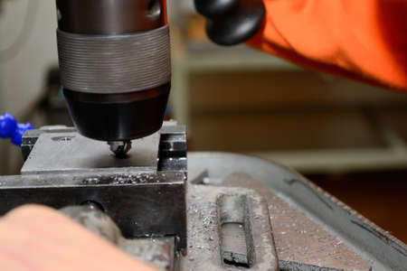 exactness: Person working in workshop with drill and countersink