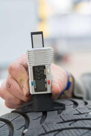 rodamiento: Persona con medidor de profundidad del dibujo mide la profundidad del dibujo de los neumáticos