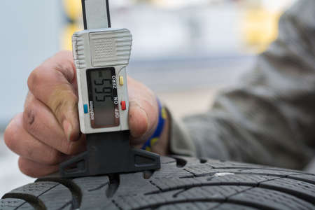 motor vehicle: Mechanic measures with profiler for winter tires, the tread depth