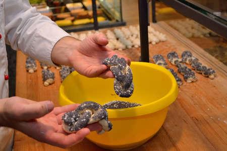 pretzel stick: Baker appeared hand in pastry poppy-salt mixture
