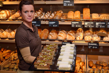saleslady: Saleswoman shows selection of cakes, breads and pastries in the background