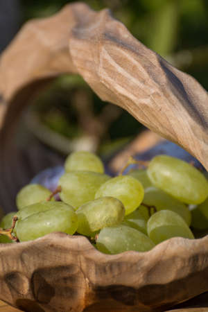 fruit bowl: green grapes in a wooden fruit bowl