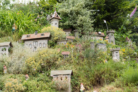 gnomos: Arbustos y modelo de un castillo con los gnomos de jardín que Landscaping Foto de archivo