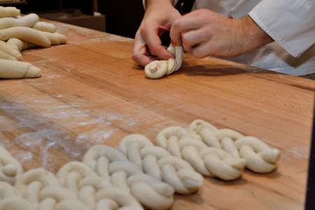 pretzel stick: Baker weaves pastries Stock Photo