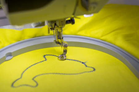 stitching machine: modern machine sews the form of a Delfin Stock Photo