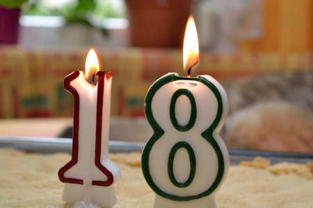 adulthood: Birthday candles with the number 18 burning to adulthood