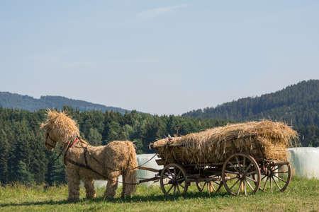 carreta madera: caballo de paja original de relleno de paja carro de madera en el campo abierto