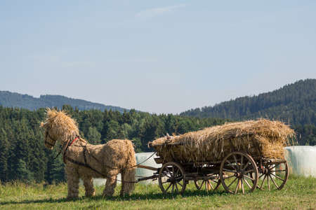 draft: original straw horse stuffed with straw wooden wagon in the open countryside