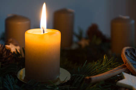 advent wreath: first candle on decorative advent wreath is burning in a dark environment