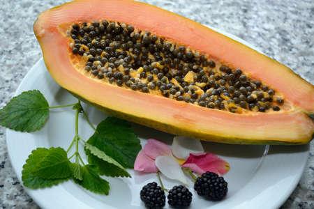 flesh colour: halved papaya with decoration on plate