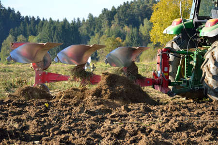 plough machine: Farmer plows his field Stock Photo