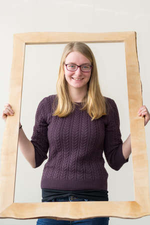 vivre: Youth friendly smiles out from a large picture frame