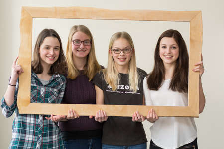 joie: Girl group smiling through picture frame - Portrait