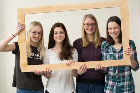 joie: four teenage girls laughing and grinning through a wooden picture frames
