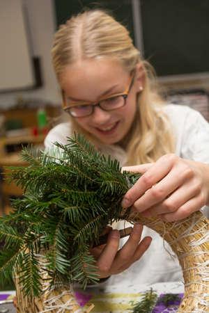 ecclesiastical: Girl making a Christmas wreath with joy