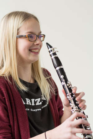 musically: happy girl holding laughing clarinet - portrait