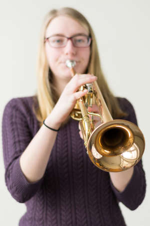 joie: Teenager playing trumpet - Focus point instrument, exempted Stock Photo