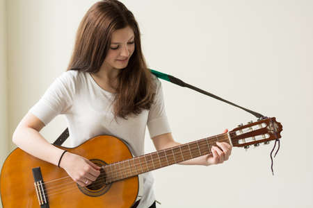 joie: Teenagers playing with a guitar - Copy Space Stock Photo