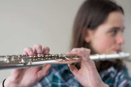 musically: Teenager playing flute - Copy Space and blurred person