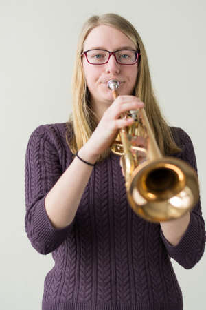 musically: Teenager playing with a trumpet - focal point Girl