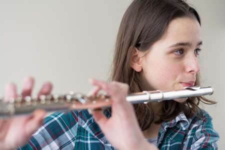 musically: Closeup of a young flute player - face focused and Copy Space