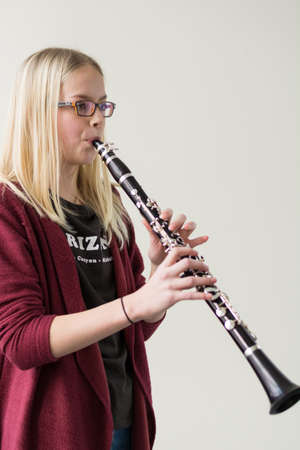 musically: preteen girl plays with a clarinet - Copy Space