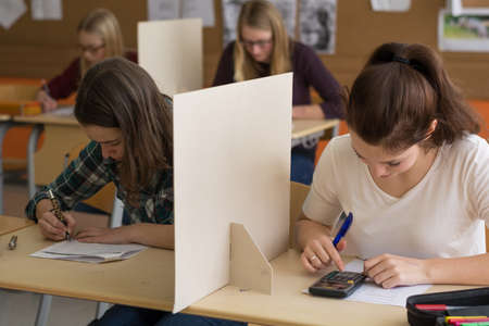 qualifications: Teenager makes in the class a test - situation with four girls Stock Photo