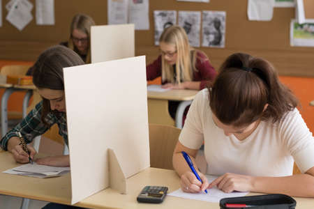 pupils: Four pupils write a test in the classroom