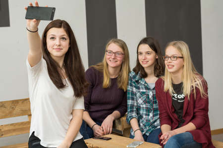 vivre: Teenager group with four girls making with a Smartphone Selfie