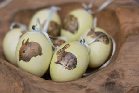 ecclesiastical: colored Easter eggs with the symbol of the Easter bunny lying in a wooden bowl