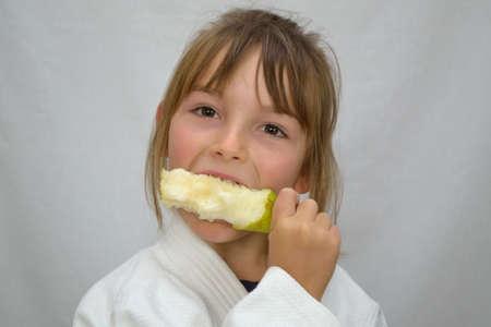 vigorously: little girl biting vigorously in a pear