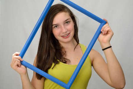 fair skinned: Girl smiling through blue picture frame - portrait