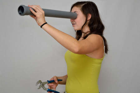 kunststoff rohr: Mädchen schaut mit Werkzeugen in der Hand durch Kunststoffrohr Lizenzfreie Bilder