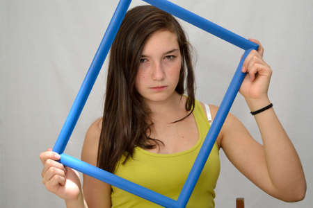 fair skinned: Teenager looking angry through a picture frame Stock Photo