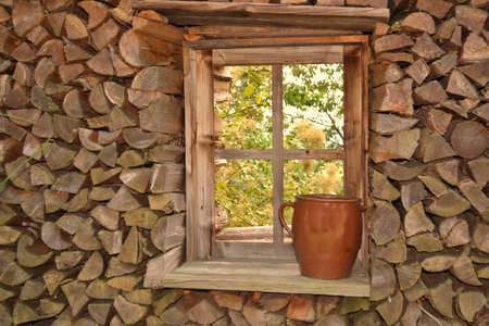 transom: stacked firewood around a wooden window Stock Photo